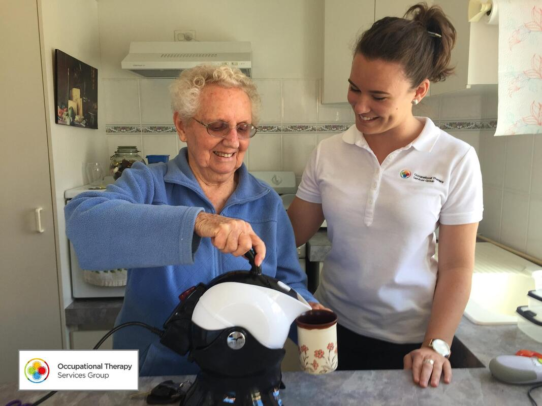 Picture of client using a kettle tipper with her Occupational Therapist standing on her left