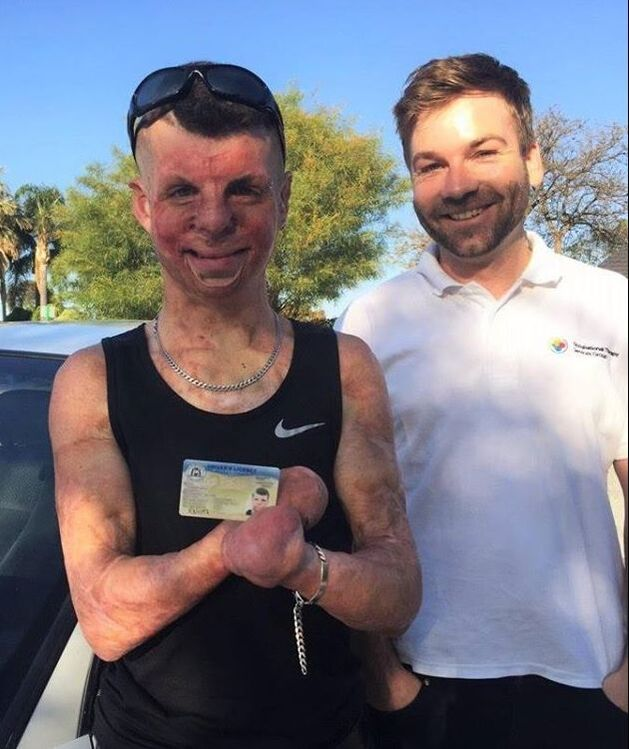 Client (left) holding his driver's licence and standing next to his Occupational Therapist (right)