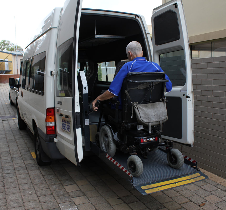 Picture of gentleman in a wheelchair entering a modified wheelchair accessible vehicle