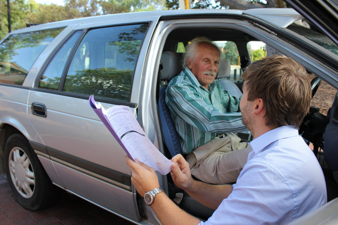 Older gentleman seated in the driver's seat with his Occupational Therapist knelt to his right