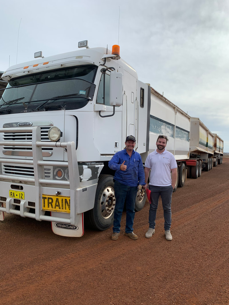 Client (left) and Occupational Therapist (right) standing next to a heavy combination truck