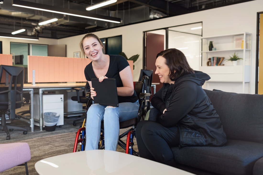 Picture of women seated in a wheelchair talking to a women seated on a couch